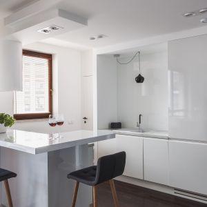 Biel i lakierowane na wysoki połysk fronty szafek wizualnie dodają kuchni kliku metrów kwadratowych. Projekt MAFGROUP