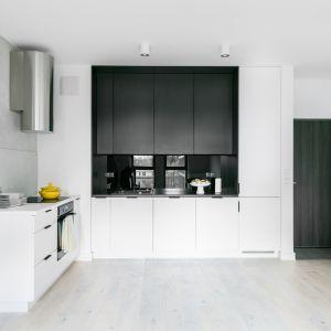 Bieł optycznie powiększa kuchnię, w połączeniu z czernią tworzy dodatkowo efekt głębi. Projekt Decoroom. Fot Pion Poziom
