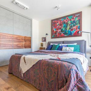 Monolityczny charakter garderoby przełamuje drewno, które optycznie poszerza przestrzeń sypialni. Projekt Monika Pniewska. Fot. Pion Poziom