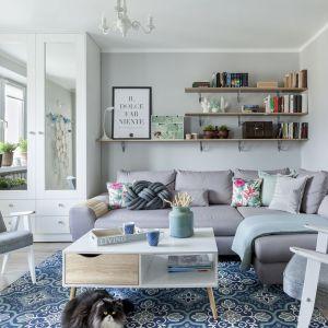 Ścianę za kanapą pomalowano na szary kolor. Powieszono na niej otwarte półki, na których ustawiono książki oraz inne elementy ozdobne. Projekt: Justyna Mojżyk. Fot. Monika Filipiu -Obałek