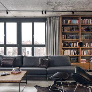 W tym salonie za kanapą znajduje się okno pięknie udekorowane szarymi zasłonami oraz fragment ściany, który zdobi drewniana, otwarta szafka na książki. Projekt: BLACKHAUS Karol Ciepliński Architekt. Fot. Tom Kurek
