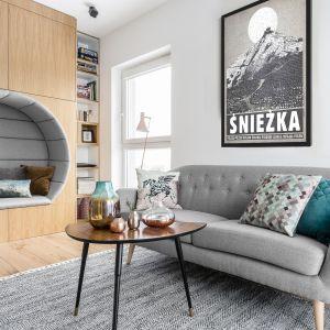 Strefę wypoczynku w salonie buduje mała, szara sofa oraz ukryte w zabudowie meblowej siedzisko - dziupla. To niezwykle oryginalny pomysł! Projekt Magma. Fot. Fotomohito