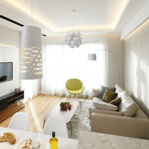 Tapeta na ścianie i żółty, designerski fotel nadają stonowanemu kolorystycznie wnętrzu aranżacyjnego pazura. Projekt Agnieszka Hajdas-Obajtek