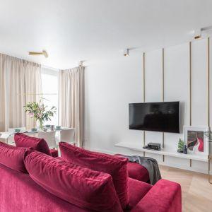 Ścianę z telewizorem zdobią złote dekoracje. Kanapę umiejscowiono naprzeciw telewizora. Projekt Decoroom. Fot. Pion Poziom