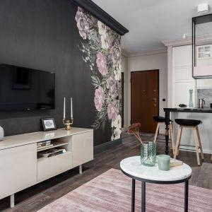 W małym salonie telewizor zawisł tuż przed stylową szafką RTV. Pomalowaną na czarno ścianę zdobi rysunek chińskich róż. Projekt JT Neptun Park