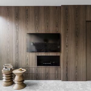 Telewizor umiejscowiono w fornirowanej zabudowie z wyraźnym rysunkiem drewna. Projekt Magma. Fot. Fotomohito.