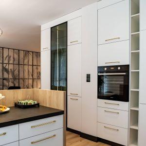 Aranżację kuchni dopełniają nieregularnie powieszone lampy oraz piękne, złote profile między płytkami. Projekt: DG Studio Donata Gadalska. Fot. Jacek Fabiszewski