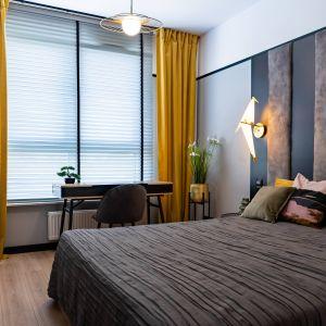 W sypialni, sprytnie ukrytej za ścianą z fototapetą, dominuje szara kolorystyka ścian i zagłówka, ocieplona żółtymi dodatkami. Projekt: DG Studio Donata Gadalska. Fot. Jacek Fabiszewski