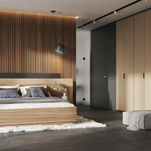Poprowadzona na całą wysokość ściany zabudowa garderobiana stanowi stonowane tło dla wyeksponowanego srewna na ścianie za wezgłowiem. Fot. Komandor