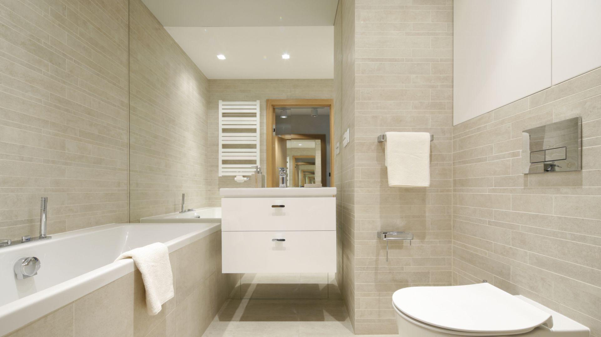Jasna kolorystka doskonale sprawdziła się w tej niewielkiej i dość wąskiej łazience. Odpowiednie zaplanowanie wszystkich elementów pozwoliło na umieszczenie w niej również wanny. Projekt: Katarzyna Uszok. Fot. Bartosz Jarosz