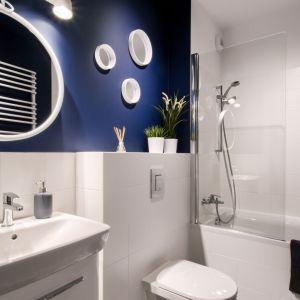 Wanna z prysznice do doskonałe rozwiązanie w tej nie za dużej łazience. Biel optycznie powiększa wnętrze, a grant dodaje charakteru. Projekt i zdjęcia:  Deer Design Pracownia Architektury