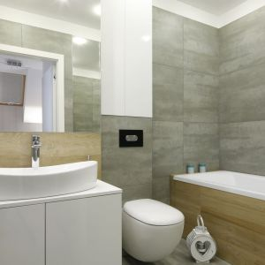 Niedużą łazienkę urządzono nowocześnie i wygodnie. Szarości i biel doskonale ocieplają płytki imitujące drewno. Mimo małego metrażu zmieściła się tu wanna. Projekt: Katarzyna Uszok. Fot. Bartosz Jarosz