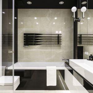 Łazienka główna utrzymana w klimacie luksusowej łazienki hotelowej z wanną oraz prysznicem również z czarnymi elementami, które pojawiają się w całym mieszkaniu. Projekt: Anna Maria Sokołowska. Fot. Fotomohito