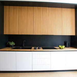 Ścianę nad kuchennym blatem zdobi czarne, matowe, piaskowane szkło, które jest jeszcze łatwiejsze w czyszczeniu niż popularny lacobel. Projekt: Sandra Maculewicz. Fot. Łukasz Pepol