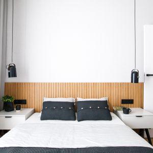 W sypialni właściciel dominują szarości. Znajduje się tutaj duża, szara szafa z drewnianymi akcentami oraz szare łóżko z pojemnikiem na pościel. Projekt: Sandra Maculewicz. Fot. Łukasz Pepol
