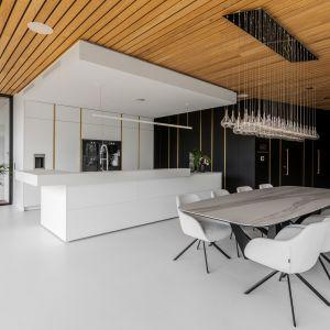 W kuchni centralny element stanowi niezwykle elegancka biała wyspa kuchenna o nowoczesnej, choć oszczędnej formie. Projekt Joanna Ochota Archimental Concept JOana. Fot. Mateusz Kowalik