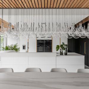 Na wyspie umiejscowiono prosty blat roboczy, umywalka i kuchenka, a wszystko oświetlone podłużną lampą w kolorze uniwersalnej bieli. Projekt Joanna Ochota Archimental Concept JOana. Fot. Mateusz Kowalik