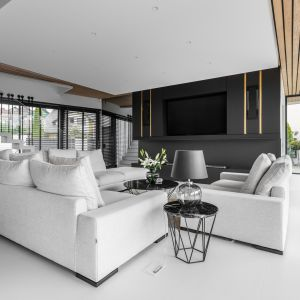 W części wypoczynkowej znalazły swoje miejsce wygodne sofy w kolorze rozbielonej szarości, nowoczesne stoliki kawowe z blatem w kolorze czarnym oraz designerski dywan, w którym zawiera się gama kolorystyczna tego domu. Projekt Joanna Ochota Archimental Concept JOana. Fot. Mateusz Kowalik