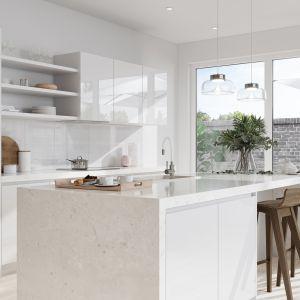 Minimalistyczna zabudowa kuchenna o frontach na wysoki połysk, bez uchwytów, z wysokiej jakości materiałów, wydaje się zlewać z bielą ściany. Fot. Ferro