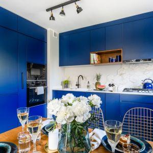 Odważna kuchnia w kolorze classic blue zestawiona z naturalnym drewnem. Projekt arch. Katarzyna Uziembło, Duet Studio. Fot. Duet Studio