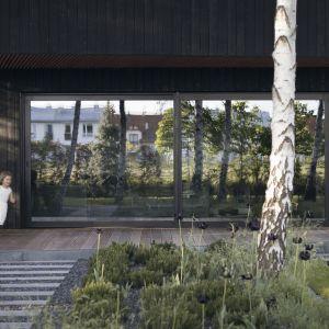 Rozległe przeszklenia pokoju dziennego łączą go funkcjonalnie i wizualnie z ogrodem.Projekt 89 Stopni. Fot. Anna Olczak