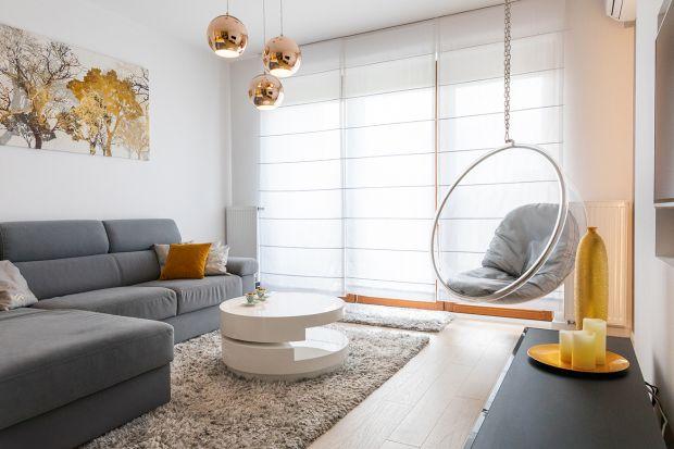 To nieduże mieszkanie urządzono lekko, nowocześnie i funkcjonalnie. Biel, drewno i złote dodatki pięknie łączą się w spójną, estetyczną całość. Do nowoczesnego wnętrza wprowadzają też nutkę klimatu glamour.<br /><br /><br
