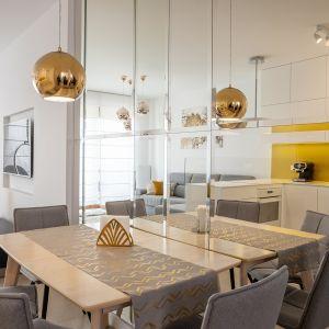 Złote lampy nad stołem w jadalni prezentują się bardzo stylowo. Projekt: Irmina Miernikiewicz. Fot. Katarzyna Dobosz