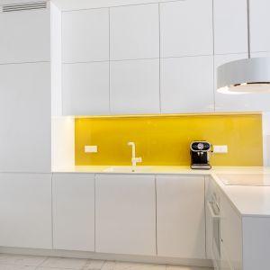 Zabudowę meblową w biały kolorze doskonale ożywia ściana nad blatem wykończona szkłem w żółto-złotym kolorze. Projekt: Irmina Miernikiewicz. Fot. Katarzyna Dobosz