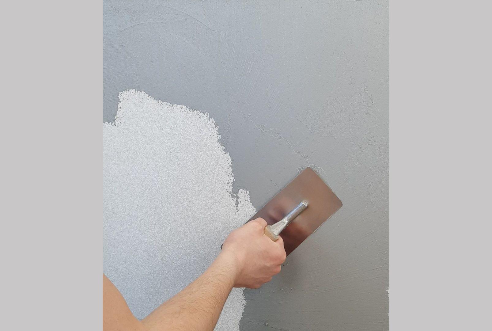 """Jeśli chcemy uzyskać efekt betonu na wykończeniu fasady, niezbędne jest wcześniejsze zabarwienie tynku modelowanego na wybrany kolor (do wyboru mamy np. jasny bądź ciemny szary oraz antracyt) i wykonanie na powierzchni charakterystycznych """"wżerów"""" za pomocą pacy. Fot. Foveo Tech"""