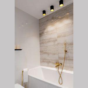 Podłogę w łazience wykończono mozaiką. Na ścianach pojawiły się zaś duże płytki imitujące onyx. Również tutaj akcesoria, lampy i armatura mają złoty kolor. Projekt: Irmina Miernikiewicz. Fot. Katarzyna Dobosz