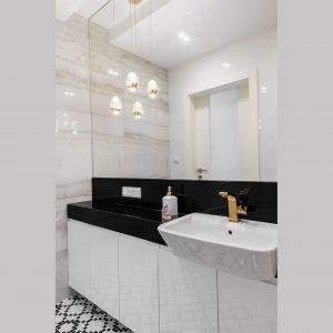 Dzięki meblom na wymiar i ogromnym lustrom udało się stworzyć w niedużej łazience elegancki klimat, a zarazem funkcjonalne wnętrze z dużą ilością miejsca do przechowywania. Projekt: Irmina Miernikiewicz. Fot. Katarzyna Dobosz
