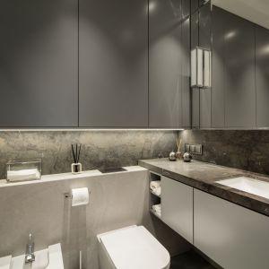 W łazience na blacie oraz ścianie pomiędzy zabudową WC i bidetu a szafką zastosowano kamień – granit Capolavoro w wykończeniu satynowanym. Projekt i zdjęcia: pracownia KODO Projekty i Realizacje Wnętrz