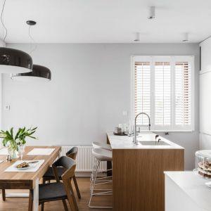 Wyspa kuchenna w drewnie jest pięknie wyeksponowana na tle czystej bieli wysokiej zabudowy. Projekt Aleksandra Kurc, Wiktor Kurc, MAKA Studio. Zdjęcia Fotomohito