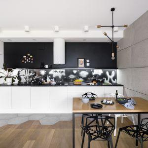 Czarny granitowy blat i pomalowana czarną, magnetyczną farbą ściana w kuchni tworzą mocny kontrast z minimalistycznymi białymi szafkami i nadają sznyt całości. Projekt Zuzanna Kuc, ZU projektuje. Zdjęcia: Łukasz Zandecki