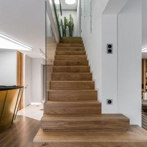 Piękne, drewniane schody ze szklaną balustradą prowadzą na piętro. Projekt: Magdalena Bielicka, Maria Zrzelska-Pawlak. Fot. Fotomohito