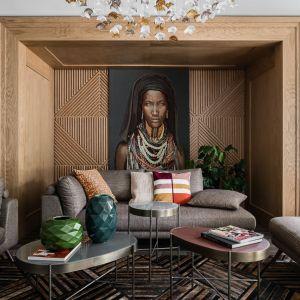 Ścianę, którą zdobi niezwykły obraz wykończono fornirowaną okładziną. Lustrzanym odbiciem jej wzoru jest dywan wybrany podczas targów w Paryżu. Projekt: Magdalena Bielicka, Maria Zrzelska-Pawlak. Fot. Fotomohito