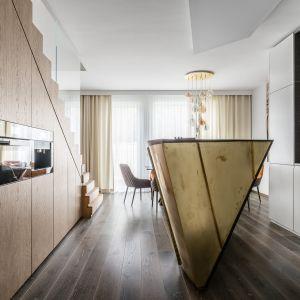 Wyspa w kuchni w złotym kolorze została wykończona mosiężną blachą z giętej płyty meblowej. Projekt: Magdalena Bielicka, Maria Zrzelska-Pawlak. Fot. Fotomohito