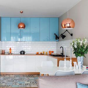 Niebieskie fronty pięknie połyskują, tworząc przytulne tło dla całej aranżacji. Projekt Decoroom. Fot. Pion Poziom