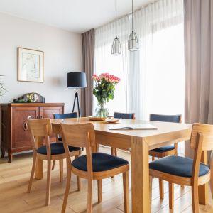 Drewniany stół i krzesła zostały wybrane z oferty polskiego producenta Fameg, lampa nad stołem i stolikiem kawowym to również polskie produkty firmy Kaspa. Projekt: Katarzyna Rohde. Fot. Marta Behling, Pion Poziom