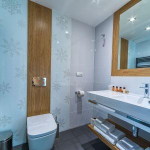 Jeżeli nie mamy miejsca na dodatkową szafkę wolnostojącą, możemy dobudować półkę np. pod zlewem. W przypadku małych łazienek dobry rozwiązaniem mogą być również wieszaki, które montuje się na grzejniku. Fot. Luxrad