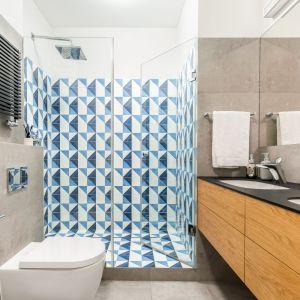 Ton aranżacji łazienki nadają małe, hiszpańskie płytki gresowe firmy Peronda w niebieskich kolorach z efektem malowania pędzlem. Neutralną bazę dla niebieskich trójkątów stanowi gres imitujący beton oraz białe ściany. Projekt: Katarzyna Rohde. Fot. Marta Behling, Pion Poziom