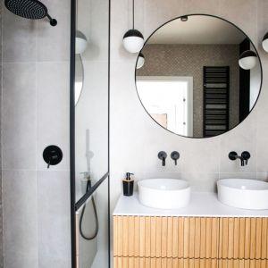 Ściany pod prysznice typu walk-in wykończony płytkami ceramicznymi w jasnym, szarym kolorze oraz nieco ciemniejszymi swoimi wyglądem przypominającymi mozaikę. Projekt: Sandra Maculewicz. Fot. Łukasz Pepol
