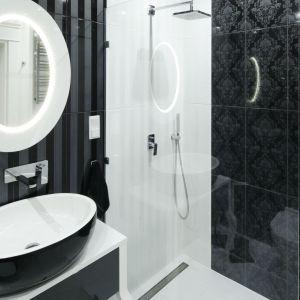 Ściany pod prysznicem zdobią białe płytki ceramiczne oraz czarne płytki imitujące tkaninę. Projekt: Katarzyna Mikulska-Sękalska. Fot. Bartosz Jarosz