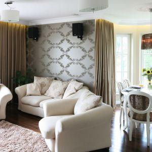 Ściana wykończona ciemną tapetą nadaje salonowi przytulności. Podobnie jak drewniana podłoga, dywan oraz zasłony. Projekt: Katarzyna Merta-Korzniakow. Fot. Bartosz Jarosz