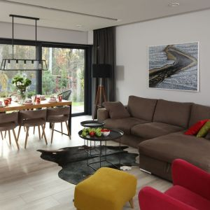 W otwartej strefie dziennej znalazło się miejsce na duży, drewniany stół oraz równie imponujących rozmiarów narożną sofę. Oba te elementy budują dwie ważne funkcjonalnie strefy we wnętrzu – jadalnianą i salonową, które choć odrębne stanowią jedną, spójną stylistycznie całość. Projekt: Laura Sulzik. Fot. Bartosz Jarosz