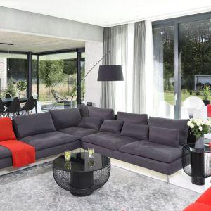 Przestrzeń na jadalnię wydzielono tuż za kanapą. Czarny stół i krzesła doskonale wpisały się w nowoczesny styl domu. Projekt: Hanna i Seweryn Nogalscy, Beton House. Fot. Bartosz Jarosz
