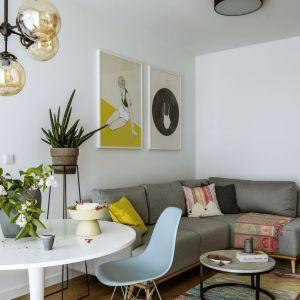 Kluczowym elementem wystroju strefy wypoczynkowo-jadalnianej jest okrągły, biały stół (Ikea), który został zestawiony z klasykami designu – pastelowymi krzesłami od Vitry oraz prostą lampą z dużymi, okrągłymi abażurami ze szkła. Projekt: Patrycja Suszek-Rączkowska, Poco Design. Fot. Yassen Hristov