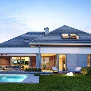 Budynek zdobią okładziny ścian z betonu architektonicznego i drewna, a duże okna otwierają wnętrze na ogród. Nazwa projektu: Hiacynt. Projekt wykonano w Pracowni MG Projekt
