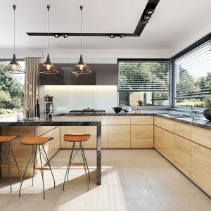 Od frontu znajduje się kuchnia otwarta na salonu, a tuż przy niej spiżarnia. Nazwa projektu: Hiacynt. Projekt wykonano w Pracowni MG Projekt