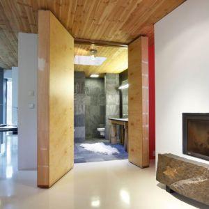 Surowa forma mebli współgra z głazem akcentującym palenisko kominka na przeciwległej ścianie. Projekt i zdjęcia: Kulczynski Architekt